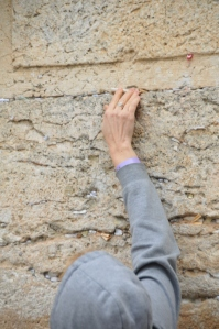 A woman tucks her prayer into a crevice at the Western Wall